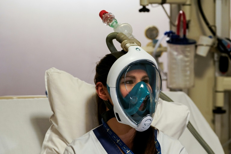A medical worker tests a Decathlon snorkelling mask, with a 3D-printed respiratory valve fitting attached, at the Erasme Hospital in Brussels.