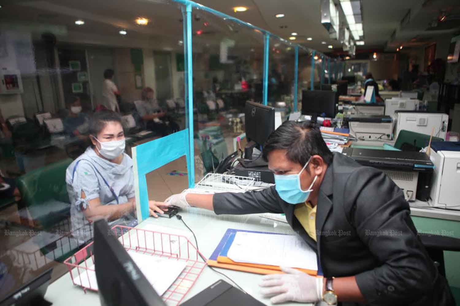 A transparent partition was installed to limit the spread of the novel coronavirus that causes Covid-19 at the Wattana district office's service outlet on Thong Lor Road in Bangkok on Monday. (Photo: Apichart Jinakukl)