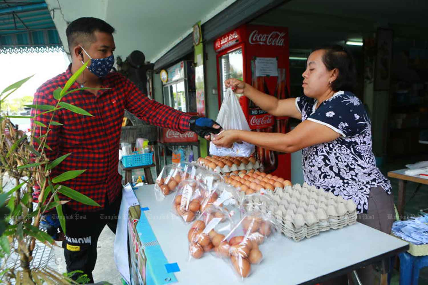 A customer buys chicken eggs at Pak Nam market in Samut Prakan province. The government has extended its ban on egg exports, and reorganised the distribution of surgical masks - to end local shortages of both items.(Photo: Somchai Poomlard)