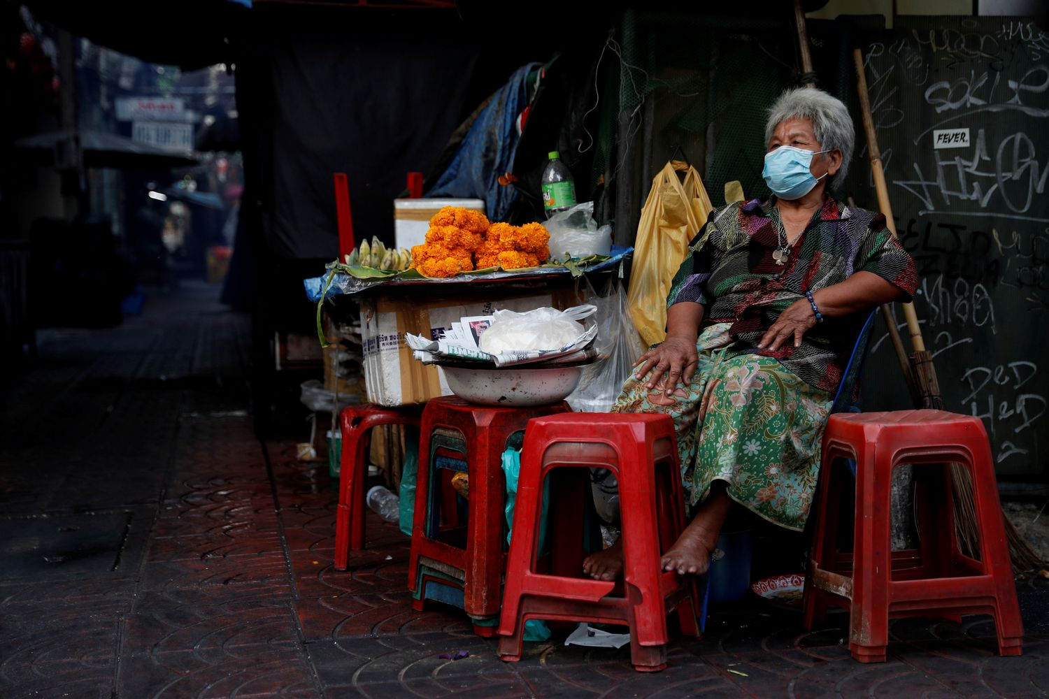 A woman wearing a protective face mask waits for customers in Bangkok on Monday. (Reuters photo)