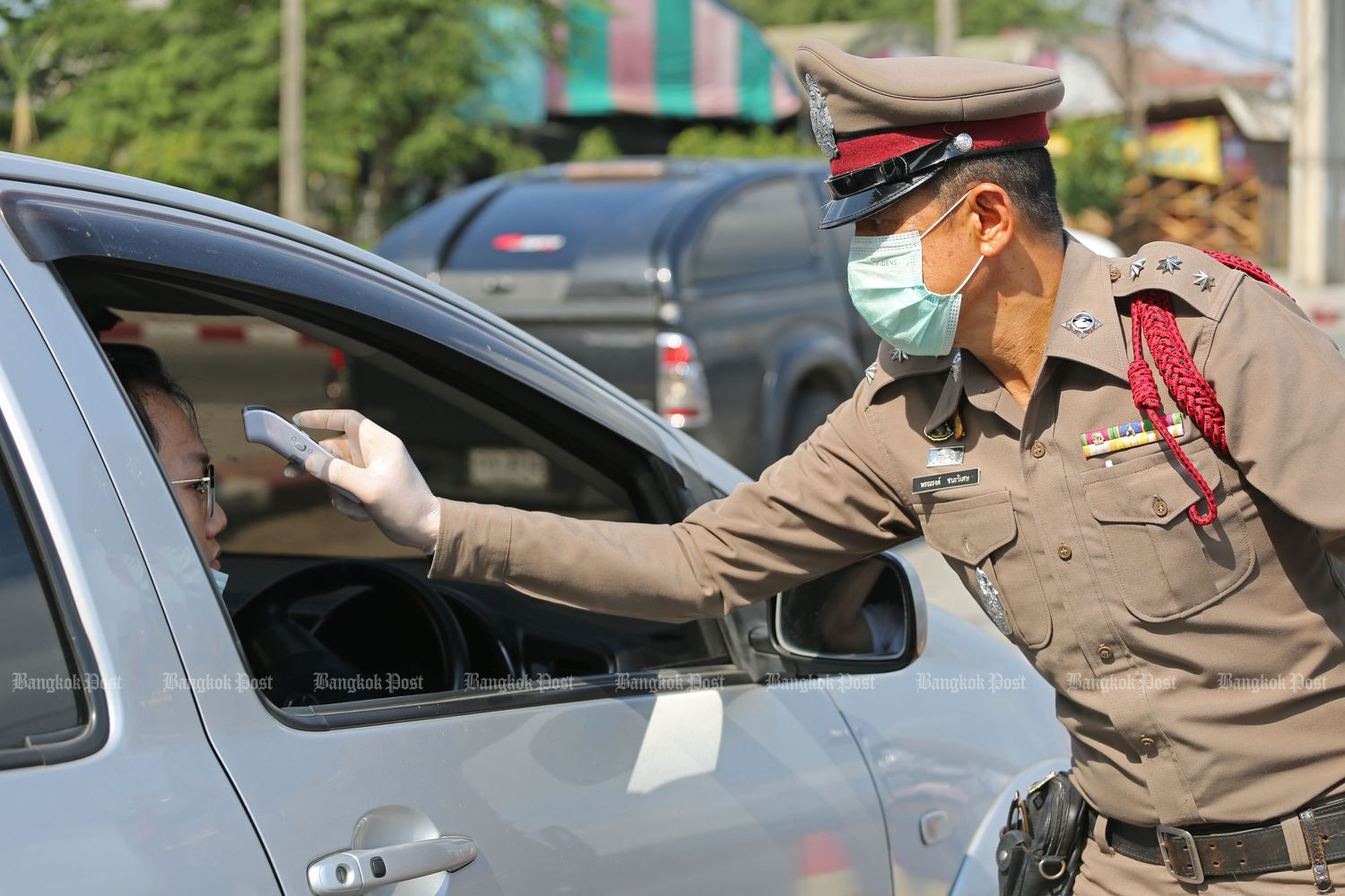 A policeman administers a fever check to a motorist on Suwinthawong Road in Bangkok on Thursday. (Photo by Varuth Hiranyatheb)