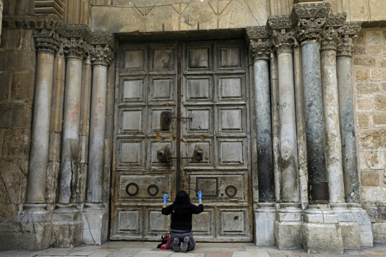 A woman prays in front of the doors of Church of the Holy Sepulchre in the Old City of Jerusalem following its closure due to the coronavirus.