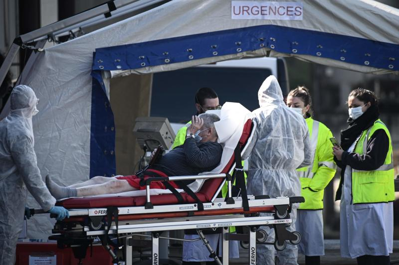 Medical personnel tend to a patient at the reception of the Emergency Room, set up in a tent, in a courtyard of the Henri Mondor Hospital in Creteil in the suburbs of Paris on Wednesday on the sixteenth day of a lockdown aimed at curbing the spread of Covid-19 (novel coronavirus) in France. (AFP)