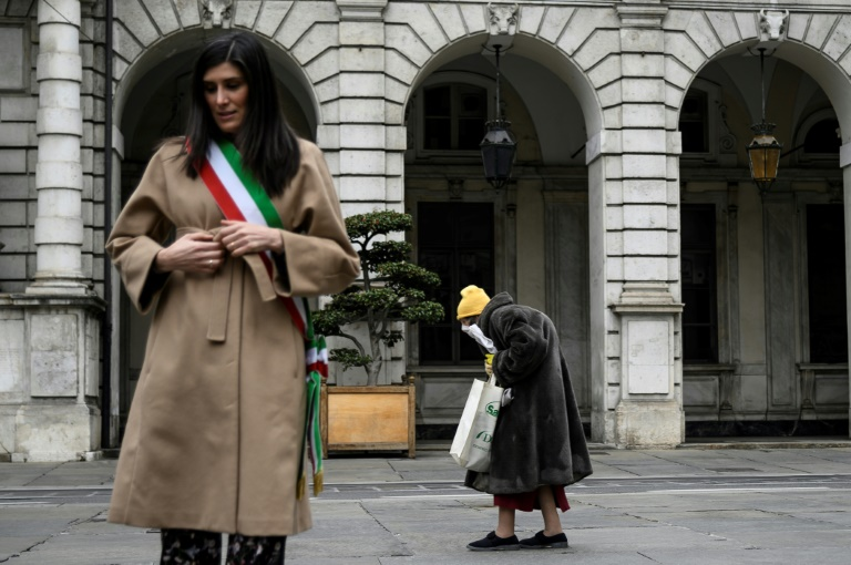 Turin mayor Chiara Appendino,left, stands at attention as an elderly woman walks past during a minute of silence in cities across Italy to commemorate the victims of the virus.