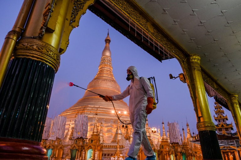 A volunteer sprays disinfectant in Shwedagon Pagoda compound as a preventive measure against the COVID-19 coronavirus in Yangon, Myanmar.