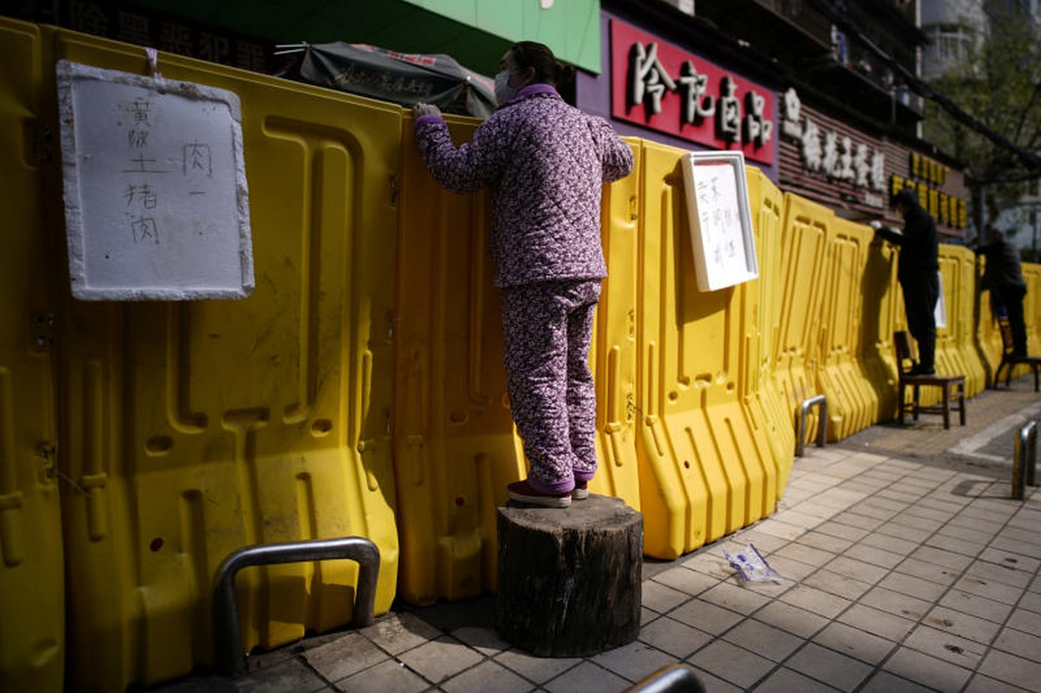 Residents buy groceries by standing on chairs and tree stumps to peer over barriers set up around a wet market on a street in Wuhan, Hubei province, the epicentre of China's coronavirus disease, on Wednesday. (Photo: Reuters)
