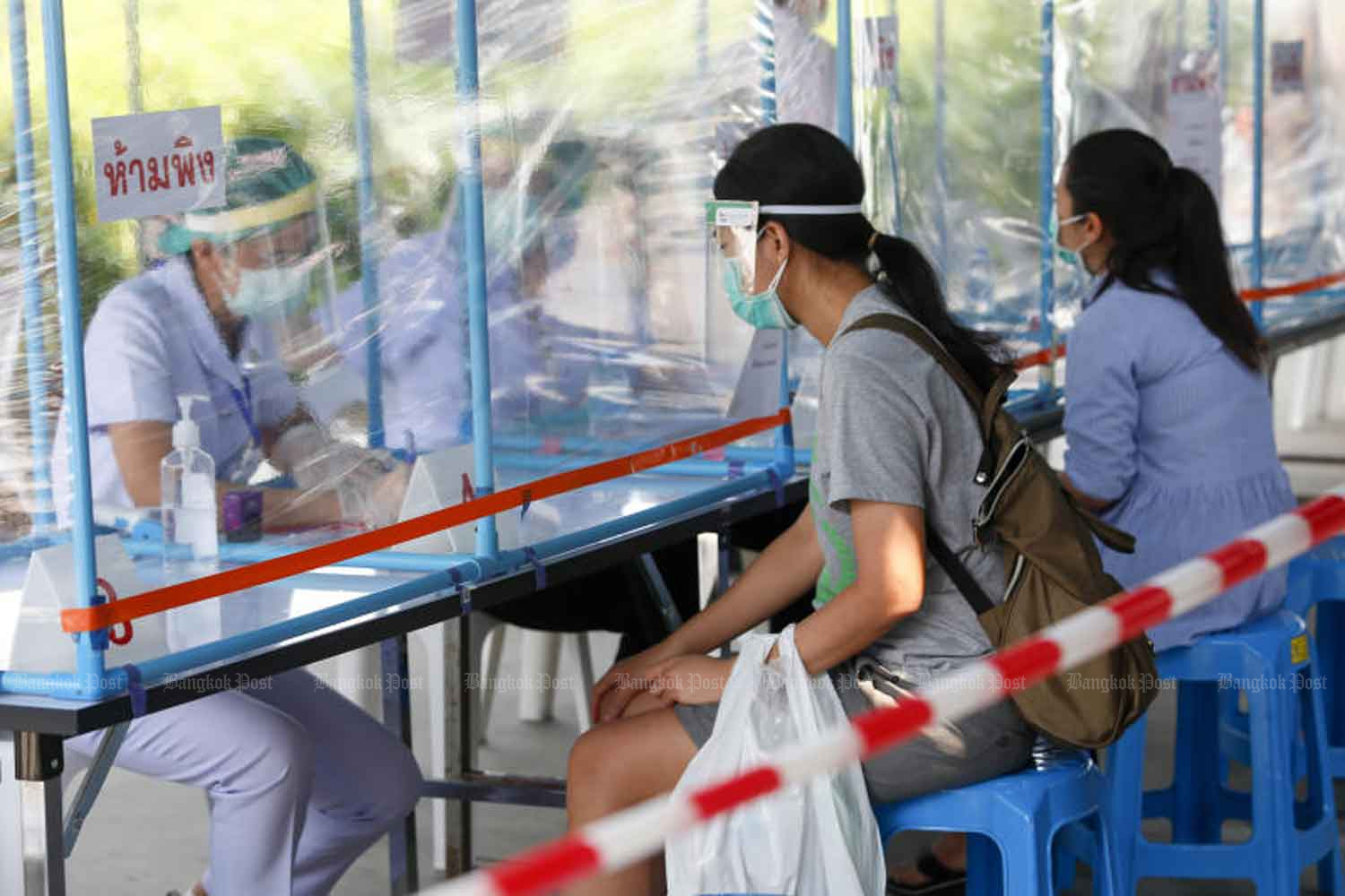 Patients and nurses are separated by a transparent partition at Pranangklao Hospital in Nonthaburi province on Thursday, when the government reported three more deaths from  Covid-19, raising the toll to 15. (Photo: Pattarapong Chatpattarasill)