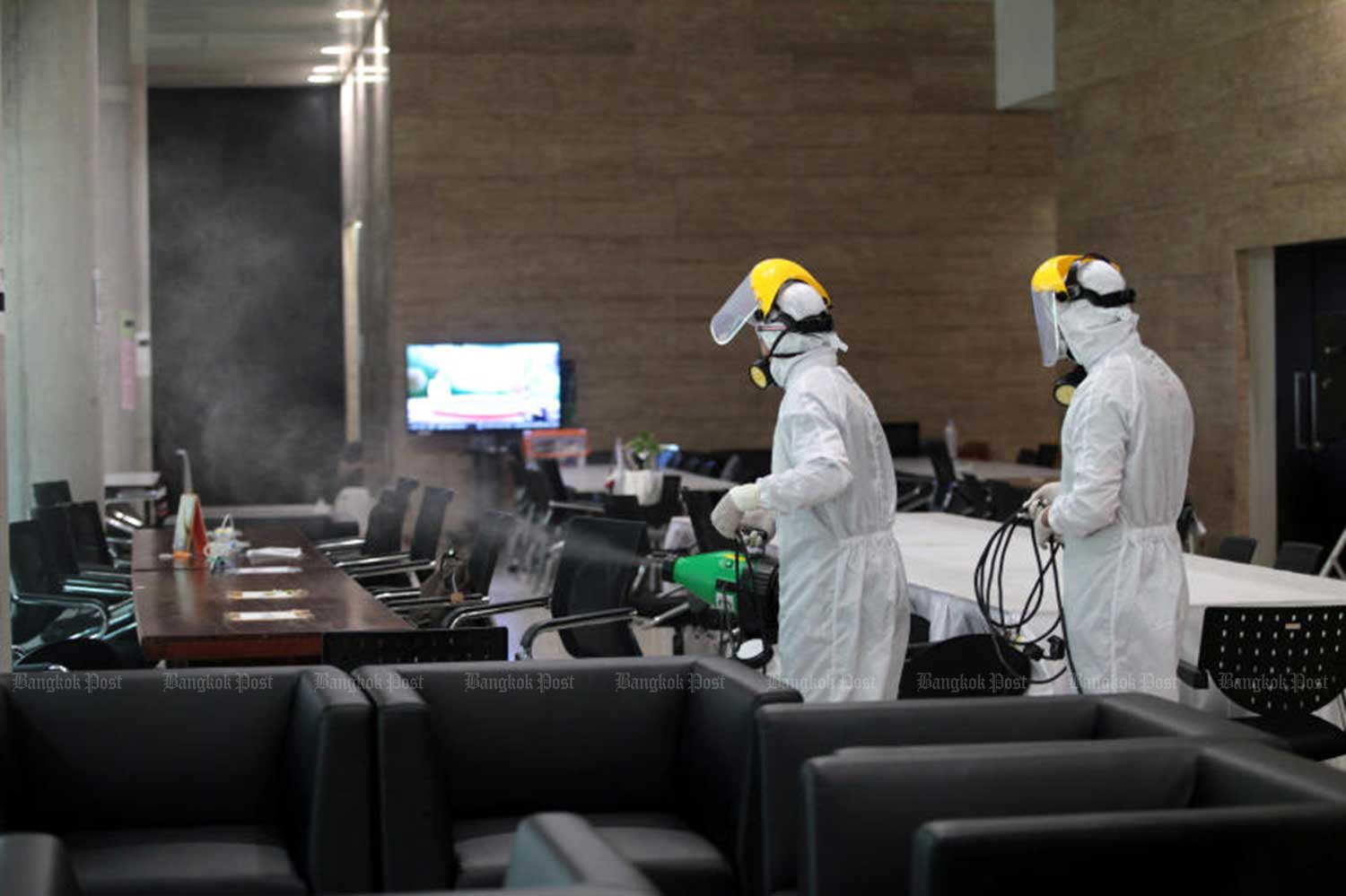 Officials spray disinfectant in the press room at Parliament, to help prevent the spread of Covid-19. (Photo by Chanat Katanyu)