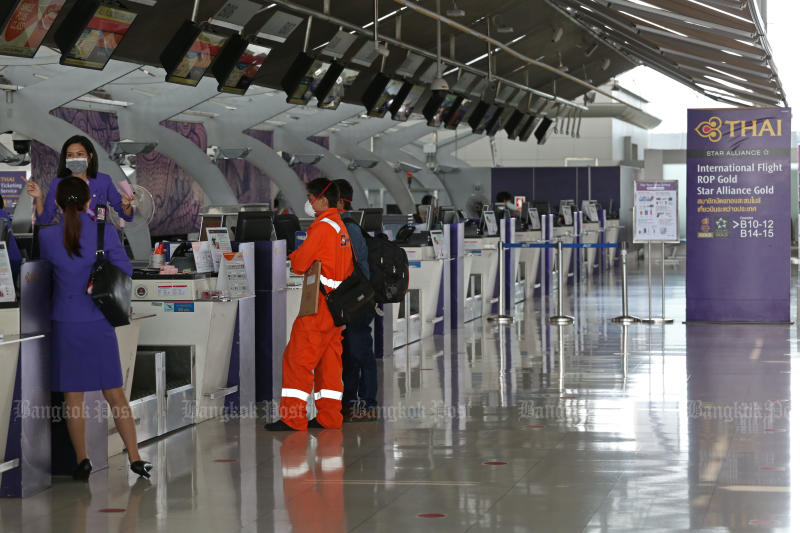 Staff of Thai Airways International at a deserted check-in area at Suvarnabhumi airport on Tuesday. (Photo by Varuth Hirunyatheb)