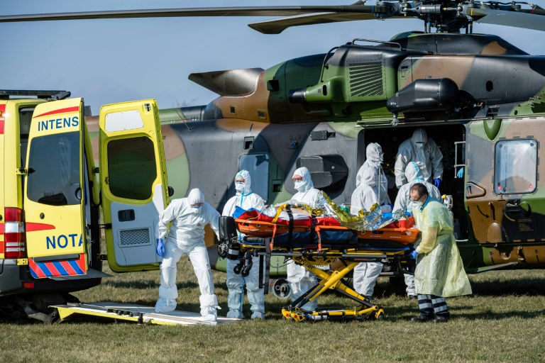 German medics take care of one of two French patients infected with the novel Covid-19 upon arrival at a little airport near Nordhausen/Harz. (Photo: AFP)