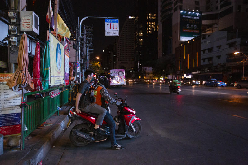 A man takes a motorbike taxi at Asok intersection on Friday ahead of a temporary curfew imposed due to the coronavirus. (Bloomberg photo)