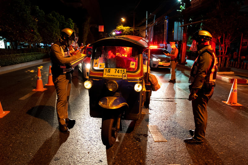 Police question people at a checkpoint in Bangkok on Friday after a curfew was imposed to prevent the spread of the coronavirus disease. (Reuters photo)