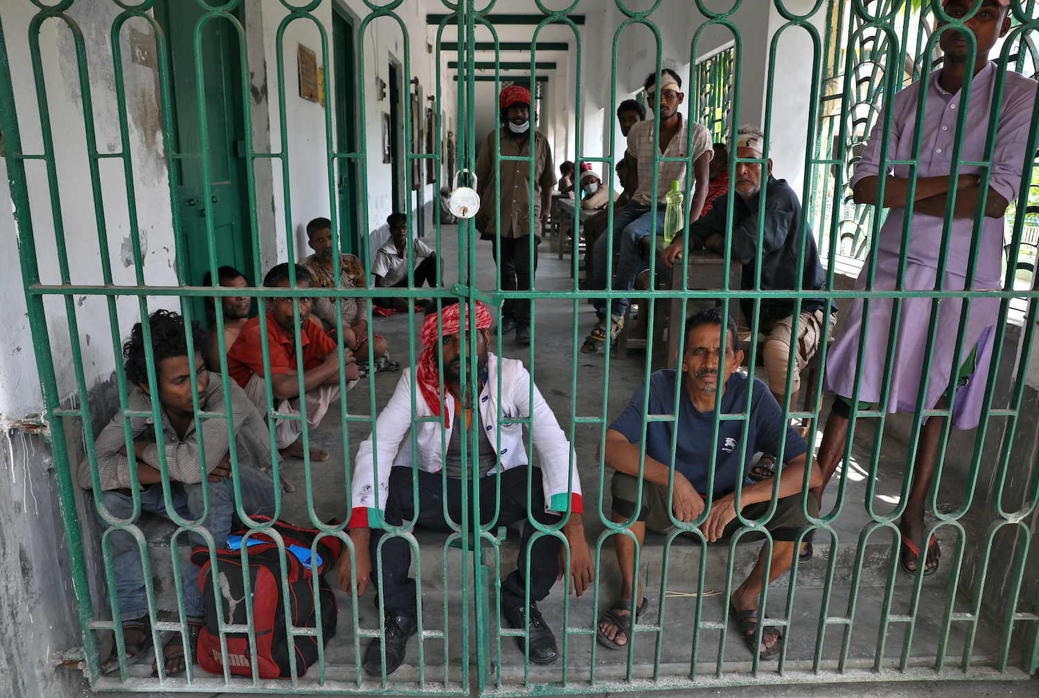 Homeless people sit in the corridor of a locked shelter where they have been confined during India's 21-day nationwide lockdown, at Howrah, on the outskirts of Kolkata. (Reuters Photo)