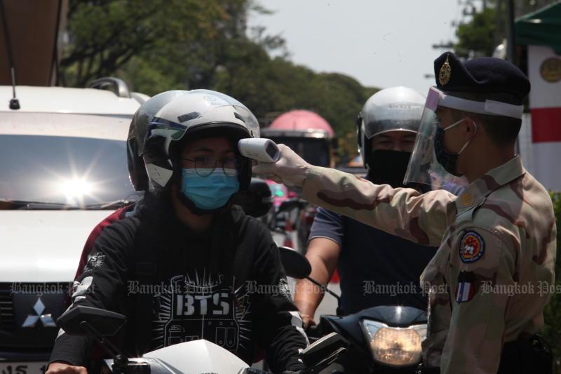 An officer checks a motorcyclist's temperature in Bangkok's Prawet district on Saturday. (Bangkok Post photo)
