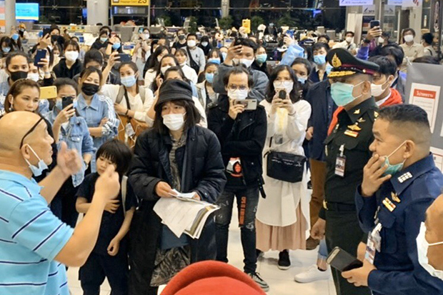 Immigration officers try to negotiate with Thai travellers who landed back in the country at Suvarnabhumi airport on Friday, saying they had not heard the government's request for overseas Thais to delay their trips back home. (Immigration Bureau photo)