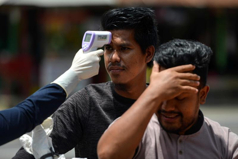 A health officer (L) checks the temperatures of motorists to help prevent the spread of the novel coronavirus at a border district checkpoint in Lamno, Aceh province on Sunday. (AFP photo)