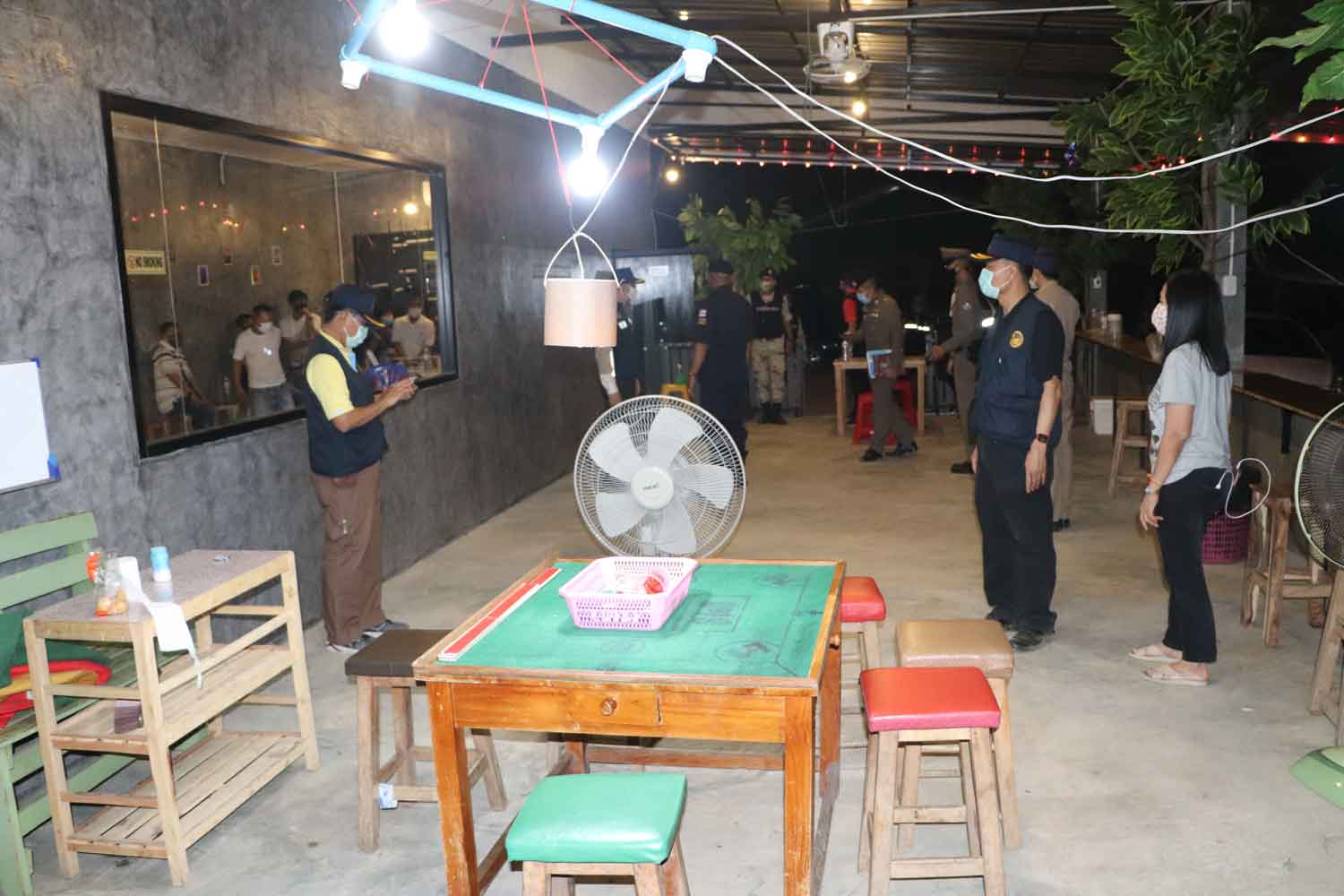 Police and administrative officials during the raid on a coffee shop where gamblers were betting on high-low, in Lampang's Muang district, on Saturday. (Photo: Assawin Pinitwong)