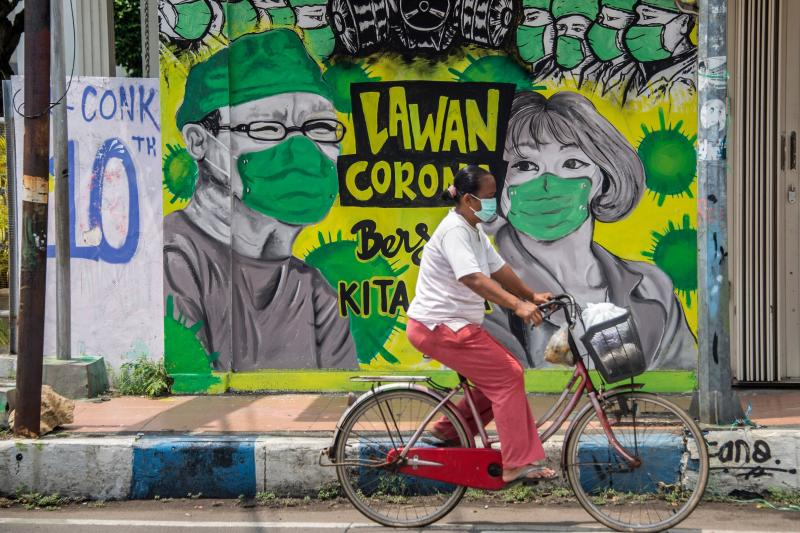 A woman cycles past a mural depicting the Covid-19 coronavirus in Bangkalan, east Java on Monday. (AFP photo)