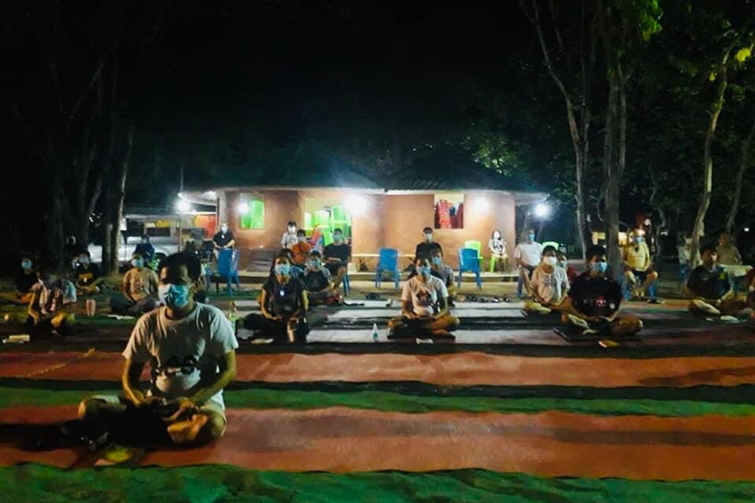 Thais from Cambodia meditate at the Pa Mok Dhammaram Buddhist centre, a place designated for state quarantine in Aranyaprathet district, Sa Kaeo province, on Sunday night. (Photo from Sawat Kate-ngam)