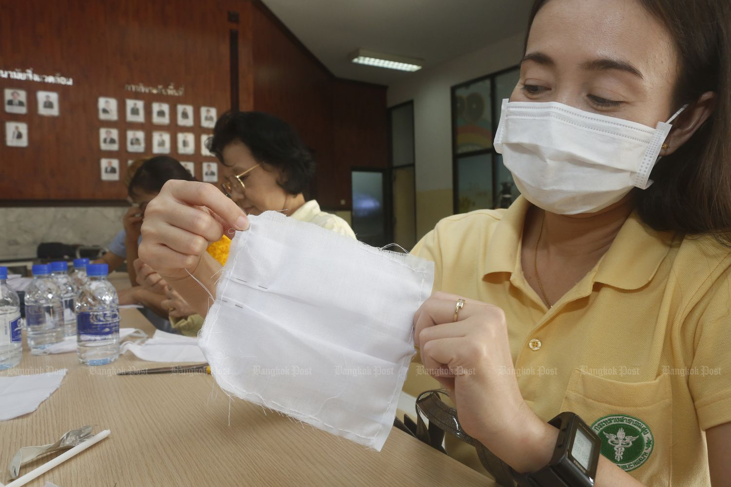 An official shows how to sew a face mask at the Public Health ministry on March 2. (Photo by Pattarapong Chatpattarasill)