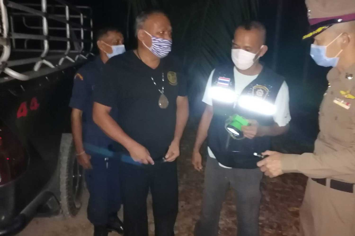 Manop Kopin, 55, head of Village Moo 9 in tambon Samor Thong of Tha Chana district, Surat Thani, centre, wearing a necklace with a large Buddhist amulet, with police at the scene where he admitted shooting dead an illustrious monk and another man in the early hours of Tuesday. (Photo: Supapong Chaolan)