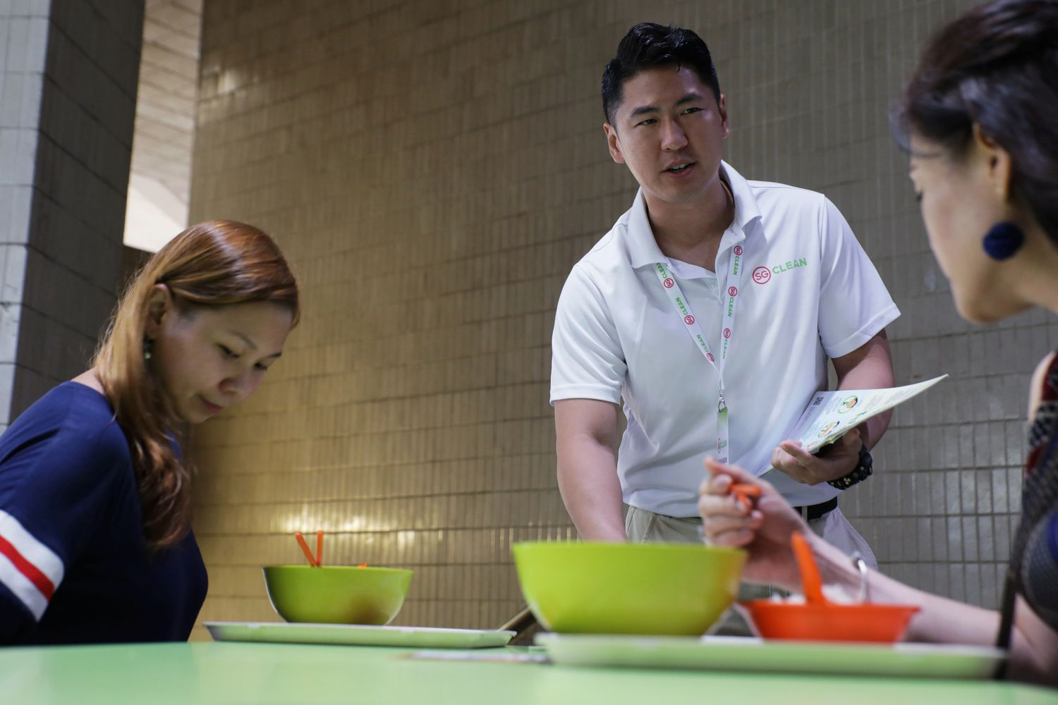 Jonathan Lau, a Jetstar pilot redeployed as a government virus awareness 'ambassador', speaks to diners about social distancing, following the outbreak of coronavirus disease at a food centre in Singapore on Friday. (Reuters photo)