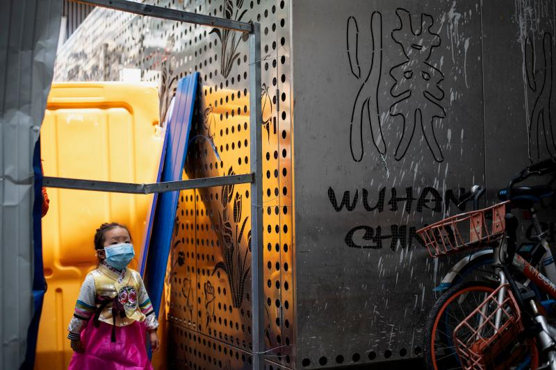 A girl wearing a face mask crosses a barricade in Wuhan, China's central Hubei province on Tuesday. (AFP photo)