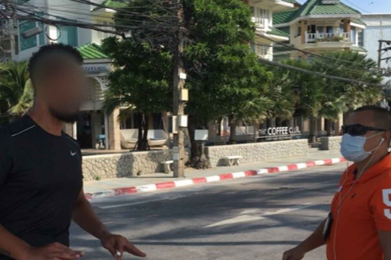 A French tourist, left, is arrested by police in Phuket for not wearing a face mask while outdoors. (Photo: Achadtaya Chuenniran)