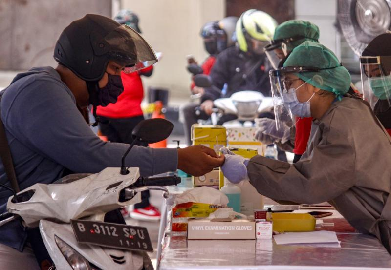 Staff from the Indonesian government's health authority (right) offer Covid-19 coronavirus rapid tests in a parking area for motorists after infections were found in the area, in Jakarta, on Wednesday. (AFP photo)