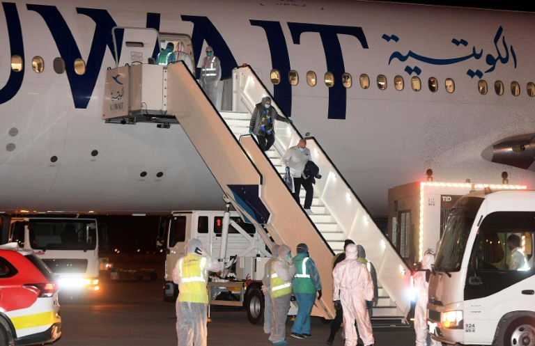 Kuwaitis returning home from Frankfurt are met by health workers in decontamination suits late last month.