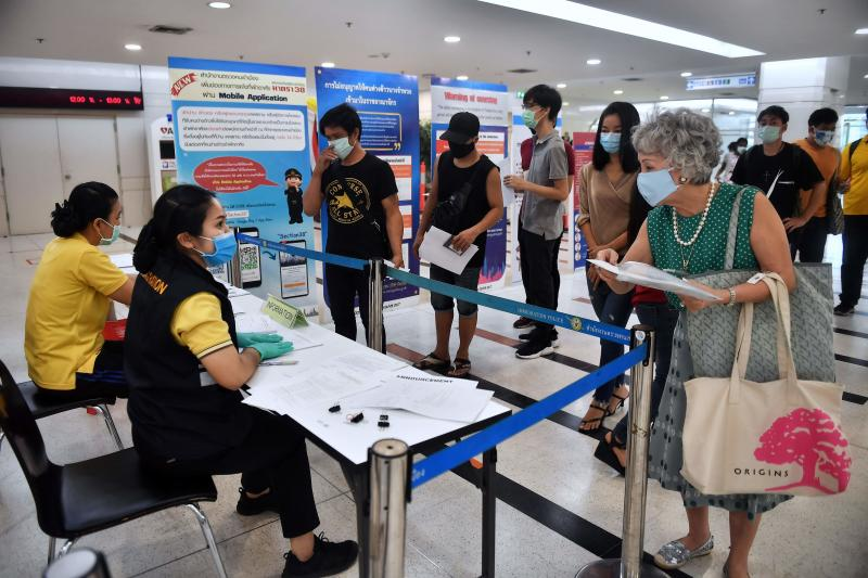 People, wearing face masks as a preventive measure against the spread of the Covid-19 novel coronavirus, queue up to renew their visas at the Government Immigration Center in Bangkok on Wednesday. (AFP photo)