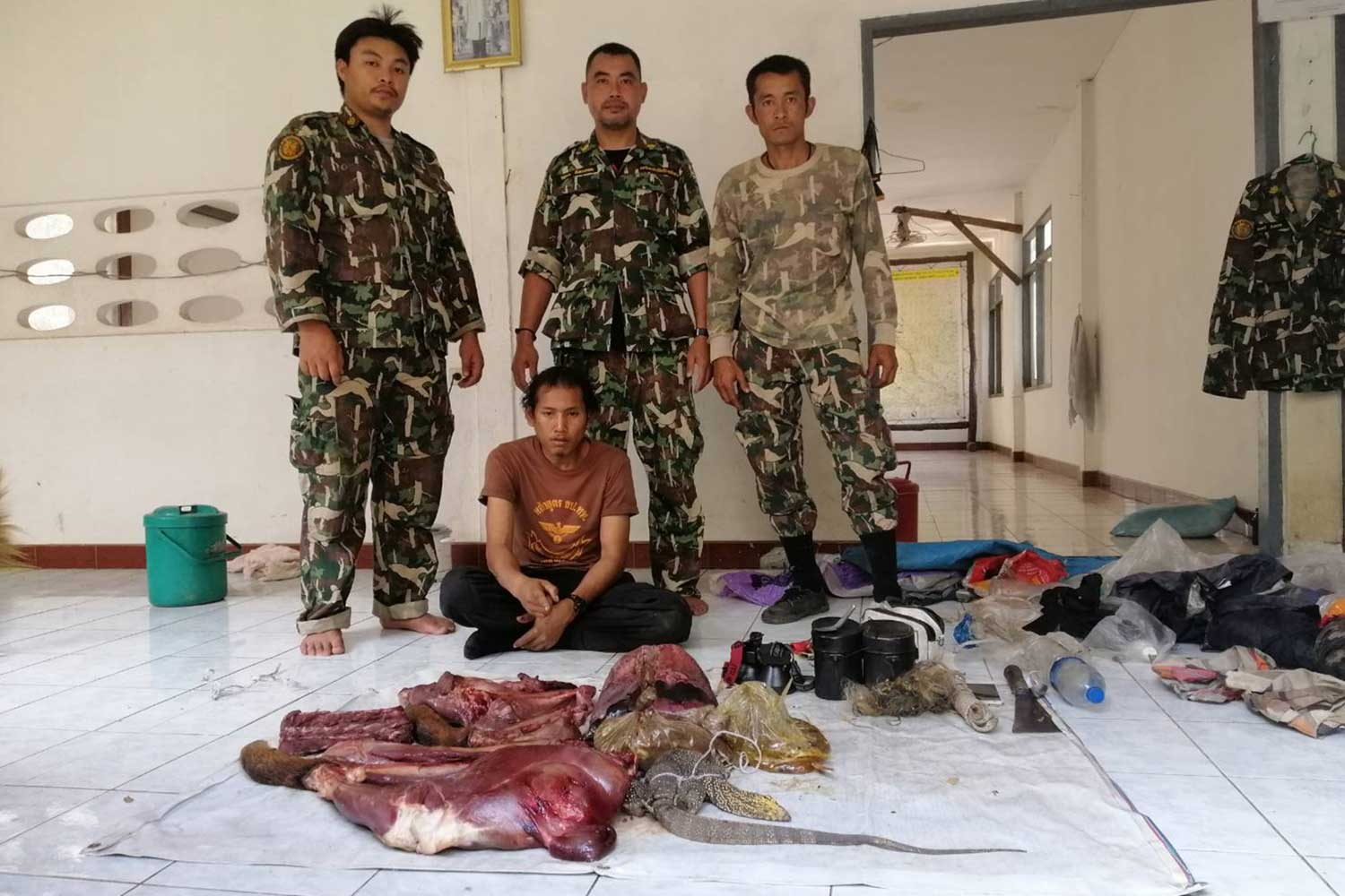 Wasin Kaki, 28, seated, after his arrest by rangers for hunting in Salak Phra Wildlife Sanctuary in Sri Sawat district of Kanchanaburi. (Photo: Piyarat Chongcharoen)