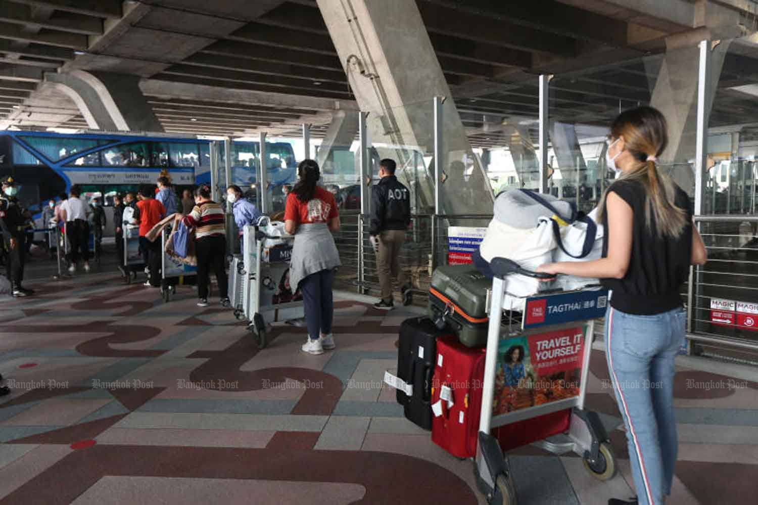Thais arrive back from Japan, at Suvarnabhumi airport in Samut Prakan province on Wednesday. Sick people were sent to hospital and the other returnees taken to a converted  hotel-quarantine facility in Bangkok. (Photo: Varuth Hirunyatheb)