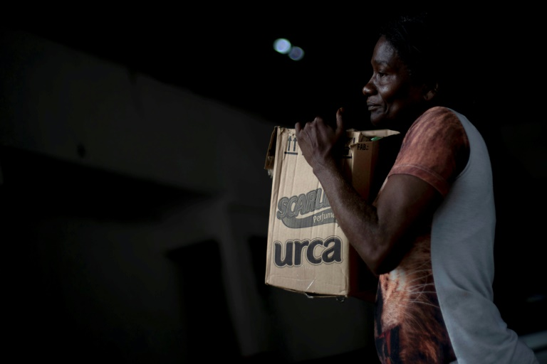 A woman in Rio de Janeiro's City of God favela carries a box with donations of basic food supplies distributed by an NGO to people suffering economic hardship during the novel coronavirus in Brazil