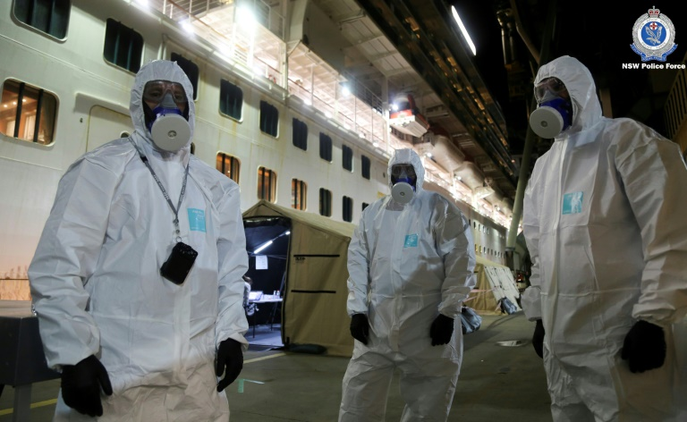 Police officers in protective gear prepare to board the coronavirus-stricken Ruby Princess cruise ship and seize its black box at Port Kembla, Australia.