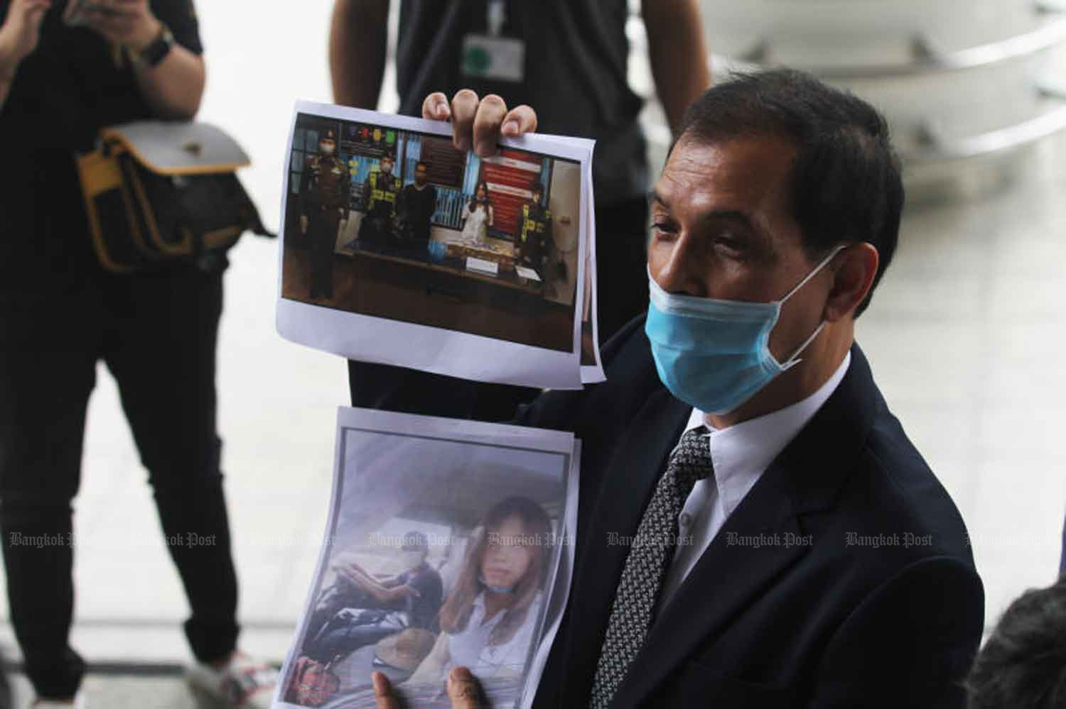 Lawyer Ananchai Chaidej shows pictures of two Myanmar suspects after their arrest.Nutthawat Wicheanbut