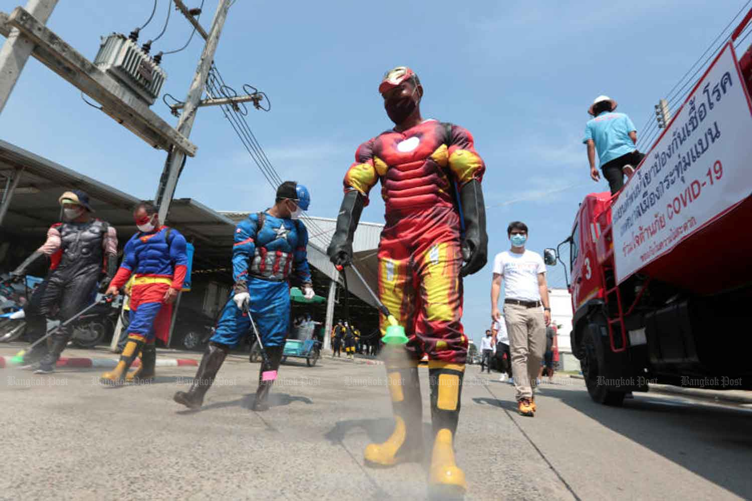 Officials in comic-hero costumes, to add a bit of cheer to sombre times, spray disinfectant at Sap Charoen Thani market in Krathum Baen district of Samut Sakhon province on Friday, part of the campaign to stop the spread of Covid-19. (Photo: Chanat Katanyu)