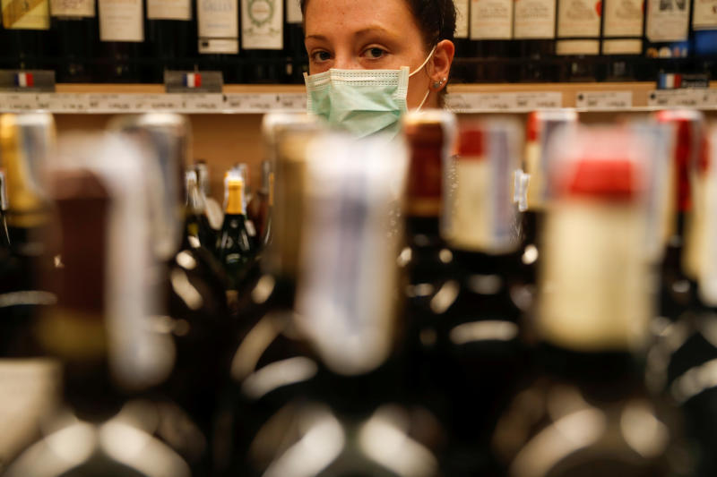 A woman wearing a protective mask aligns bottles on shelves inside a liquor store in Bangkok, after the capital announced a 10-day ban on alcohol sales from Friday. (Reuters photo)