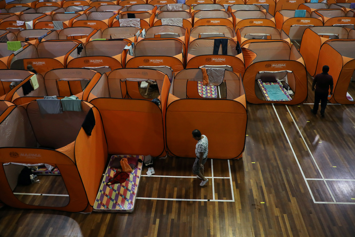 Homeless people rest inside cubicles at a temporary shelter set up in a gymnasium in Kuala Lumpur line with movement control orders being enforced in Malaysia. (Reuters Photo)