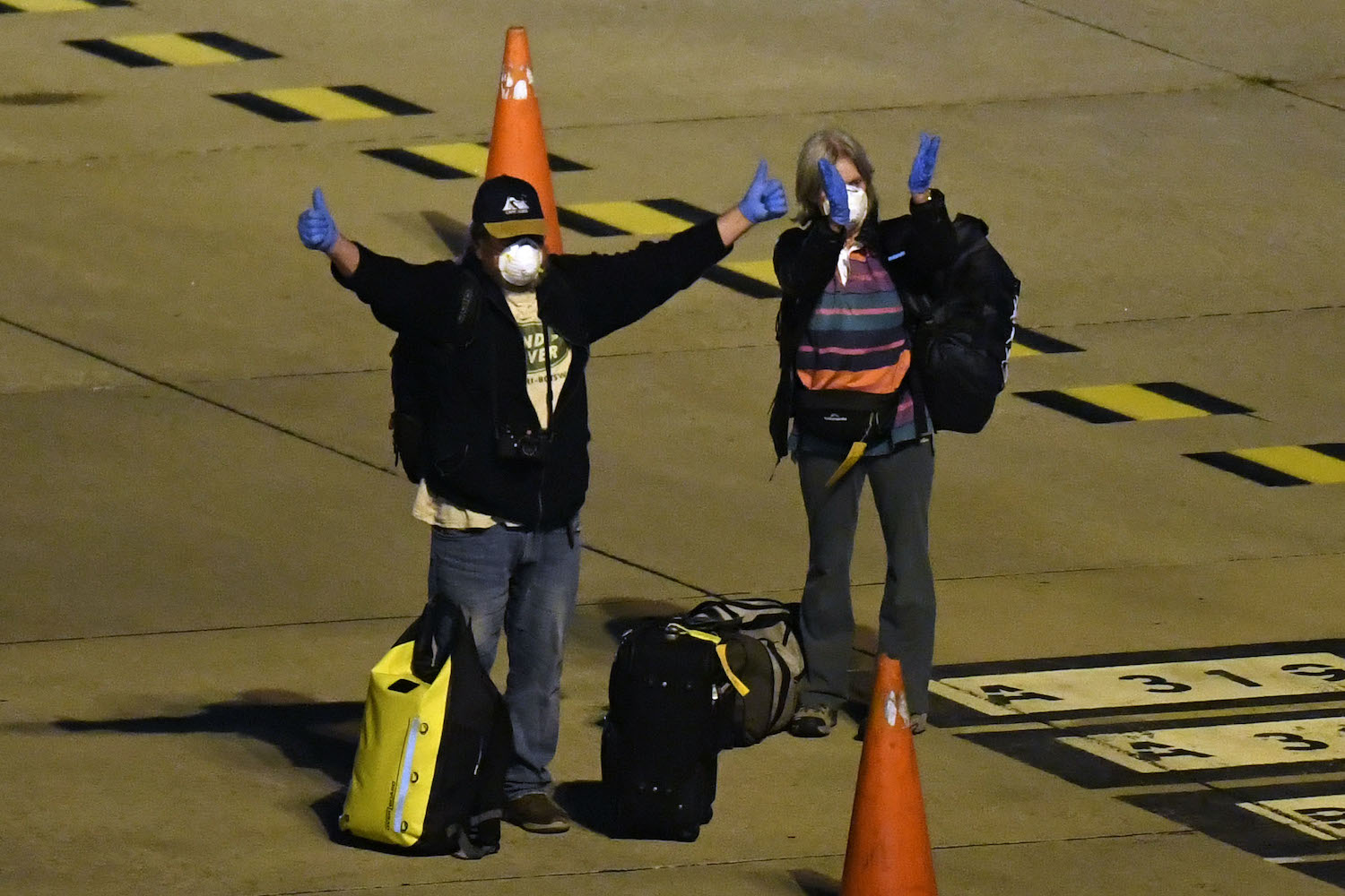 Two Covid-19-free passengers evacuated from the coronavirus-stricken Australian liner Greg Mortimer wave before boarding a plane that will fly Australian and New Zealander passengers to Melbourne, at Carrasco International Airport in Montevideo, Uruguay. (AFP Photo)