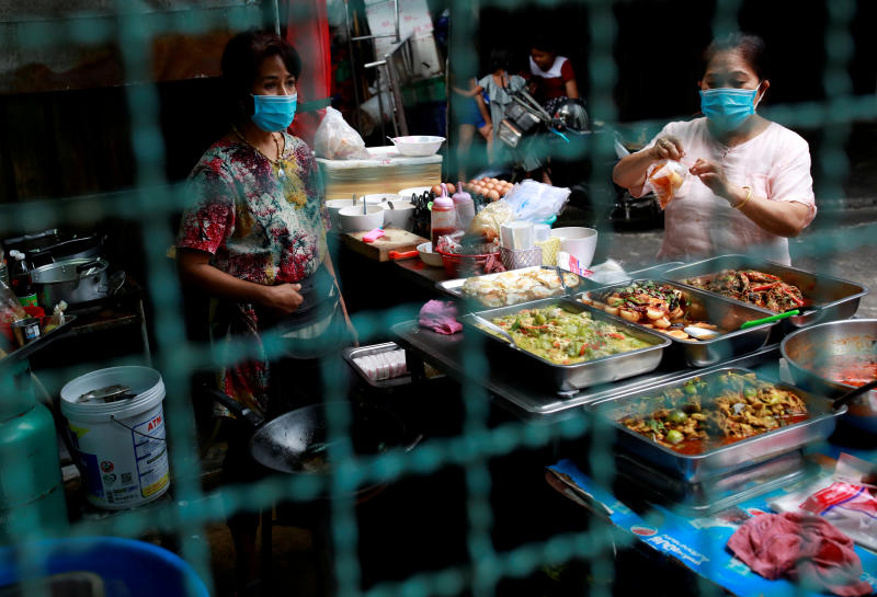 Vendors wearing protective face masks sell foods in a market during the coronavirus disease (Covid-19) outbreak in Bangkok on Saturday. (Reuters photo)