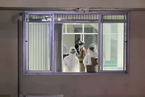 Police and health workers at the fifth floor window from where a quarantined man jumped to his death at a hospital in Phra Pradaeng district of Samut Prakan early on Monday. (Photo by Sutthiwit Chayutworakan).