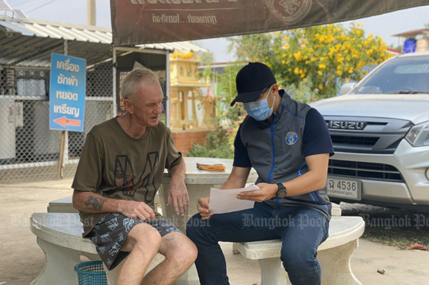 A Crime Suppression Division officer shows William Petrie the warrant for his arrest at his home in Plaeng Yao district of Chachoengsao on Sunday. (Photo supplied)