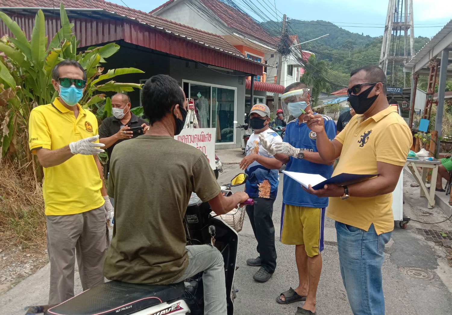 Officials and volunteers manning a screening checkpoint in Phuket stops a motorcyclist wanting to pass the checkpoint for screening checks. (Photo by Achadtaya Chuenniran)