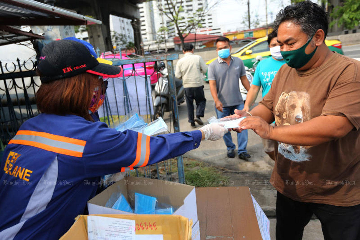 Staff of the Ek Crane logistics firm hand out free face masks to people on Bang Na-Trat Road in Bangkok on Tuesday. (Photo by Wichan Charoenkiatpakul)