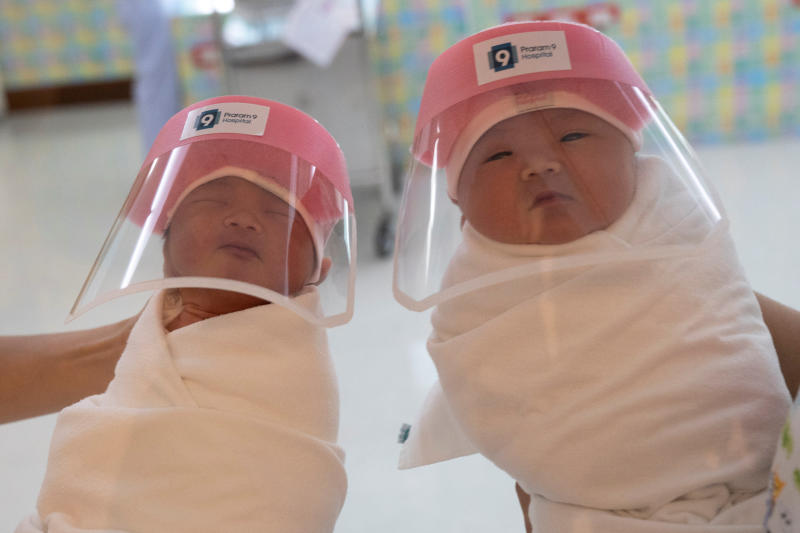 Nurses hold newborn babies wearing protective face shields during the coronavirus disease (Covid-19) outbreak at the Praram 9 hospital in Bangkok, April 9, 2020. (Reuters photo)