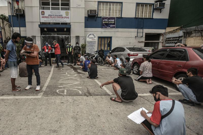 Members of the public, detained for roaming the streets without relevant passes amid the Covid-19 coronavirus pandemic, squat at a distance from one another as they are processed outside a police station at Quezon City in Manila on Tuesday. (AFP photo)