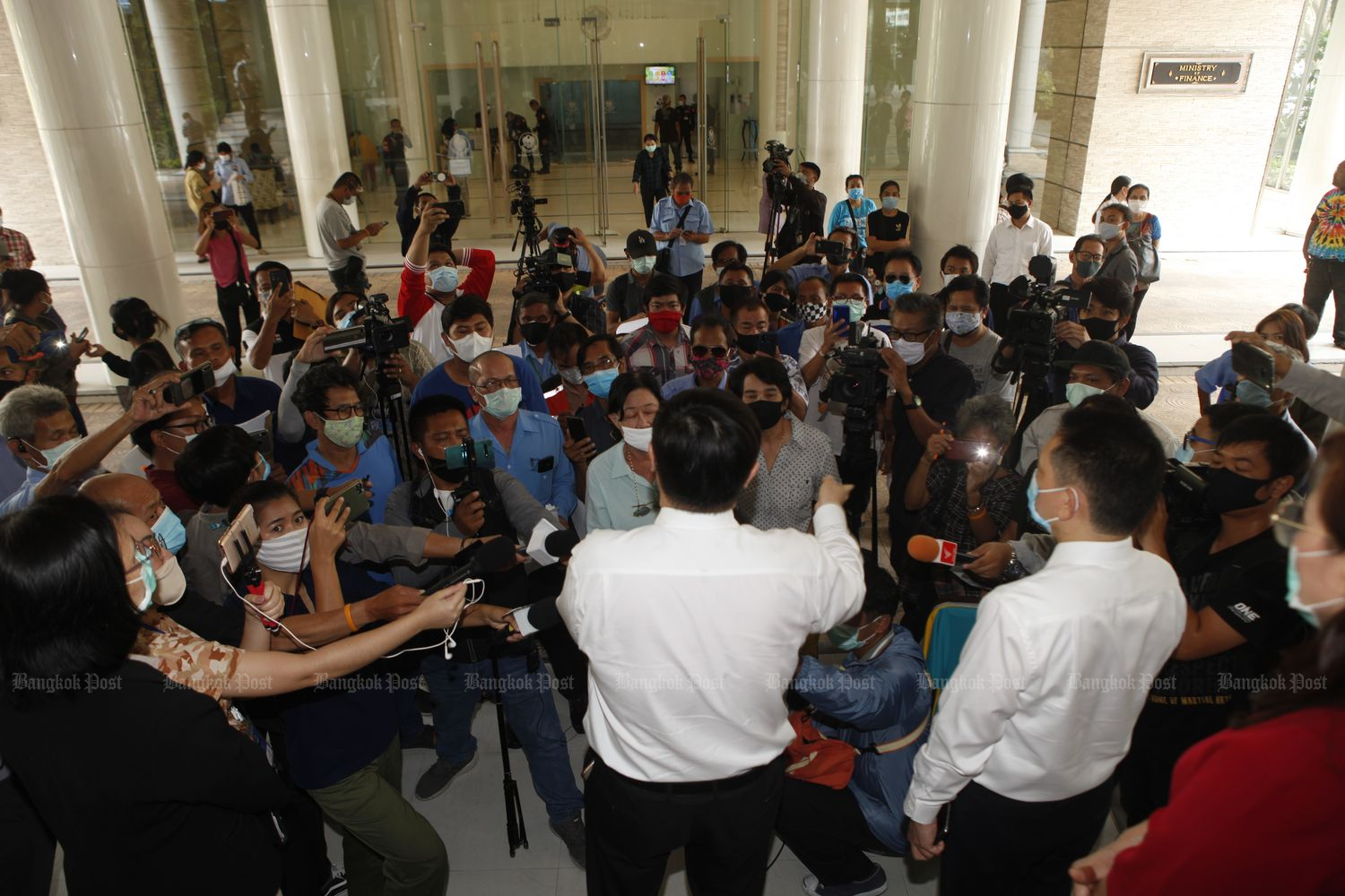 Dozens of people whose applications for the 5,000-baht aid was turned down gather at the Finance Ministry in Bangkok to demand explanations on Tuesday. (Photo by Nutthawat Wicheanbut)