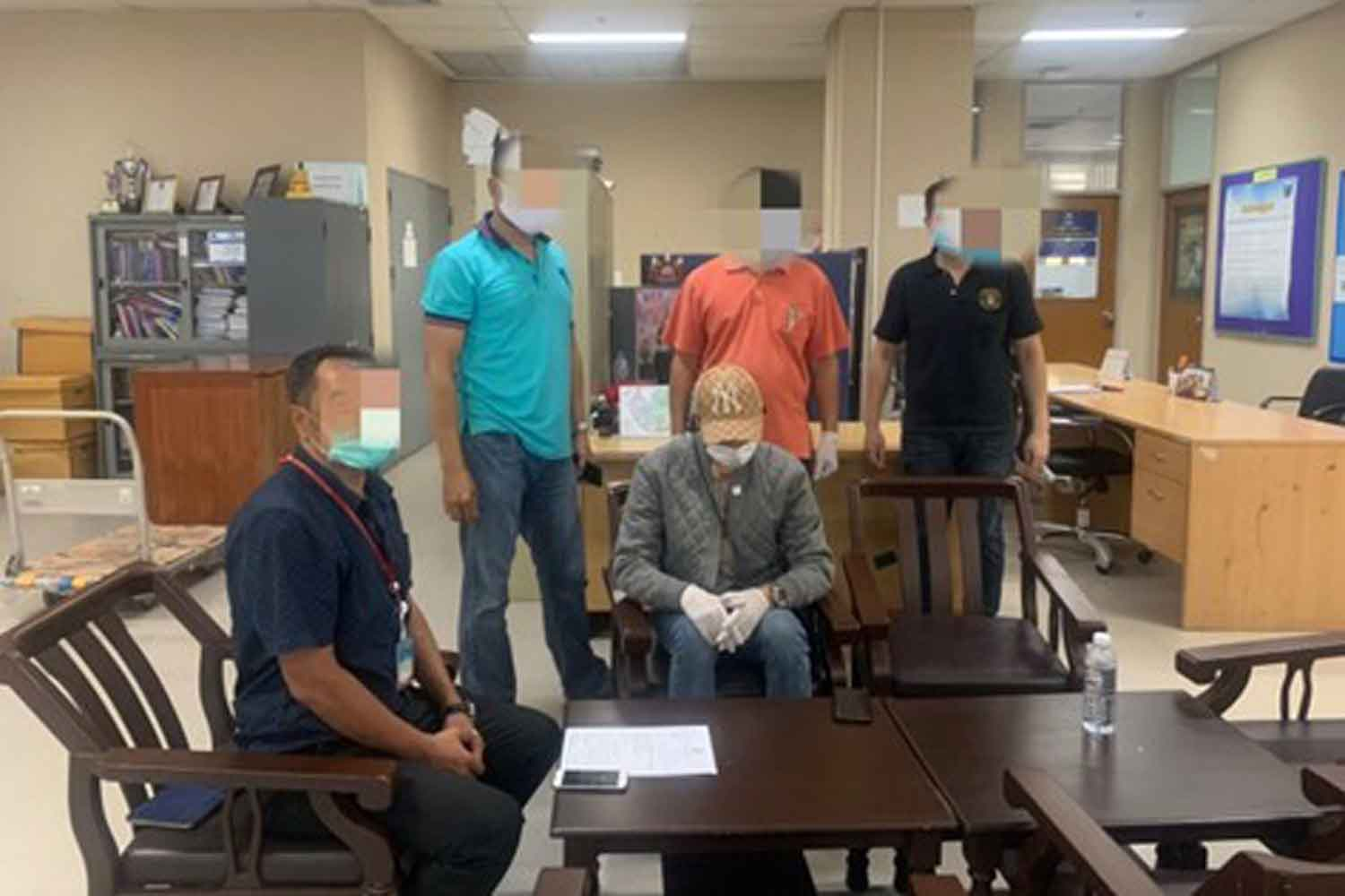 A suspect in the Forex-3D Ponzi scheme, seated right, in his apartment on Ratchadapisek road when he was arrested by Department of Special Investigation officials on Tuesday. (DSI photo)