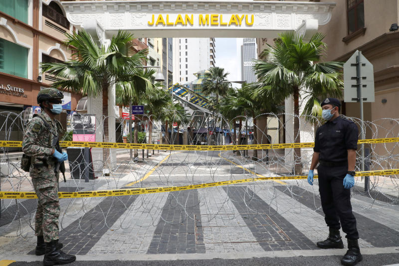 A soldier and a police officer stand guard at an entrance to a red zone under enhanced lockdown  due to the outbreak of the coronavirus disease (Covid-19), in Kuala Lumpur, Malaysia on Wednesday. (Reuters photo)